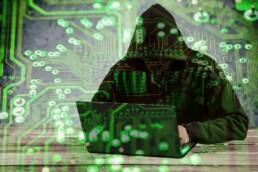 man in hoodie hacking on his laptop