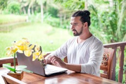 a white male with a man bun working on a laptop