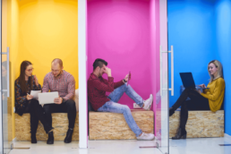 employees of a startup meeting in small colorful conference rooms