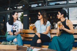 three women drinking beer an an outdoor table at bar/restaurant